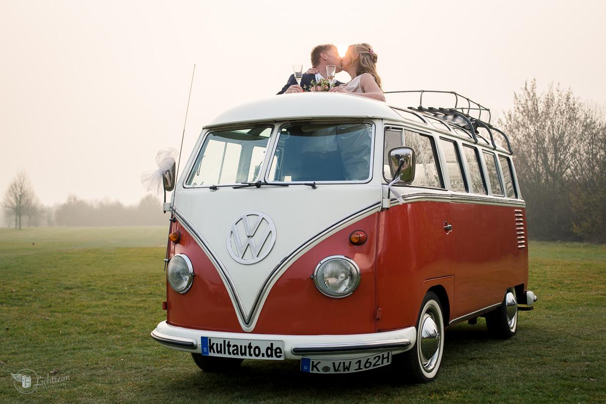 VW Bus mit Hochzeitspaar auf Golfplatz